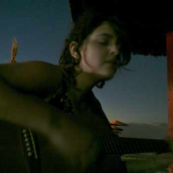 Photo of Shelley singing and playing guitar on the beach