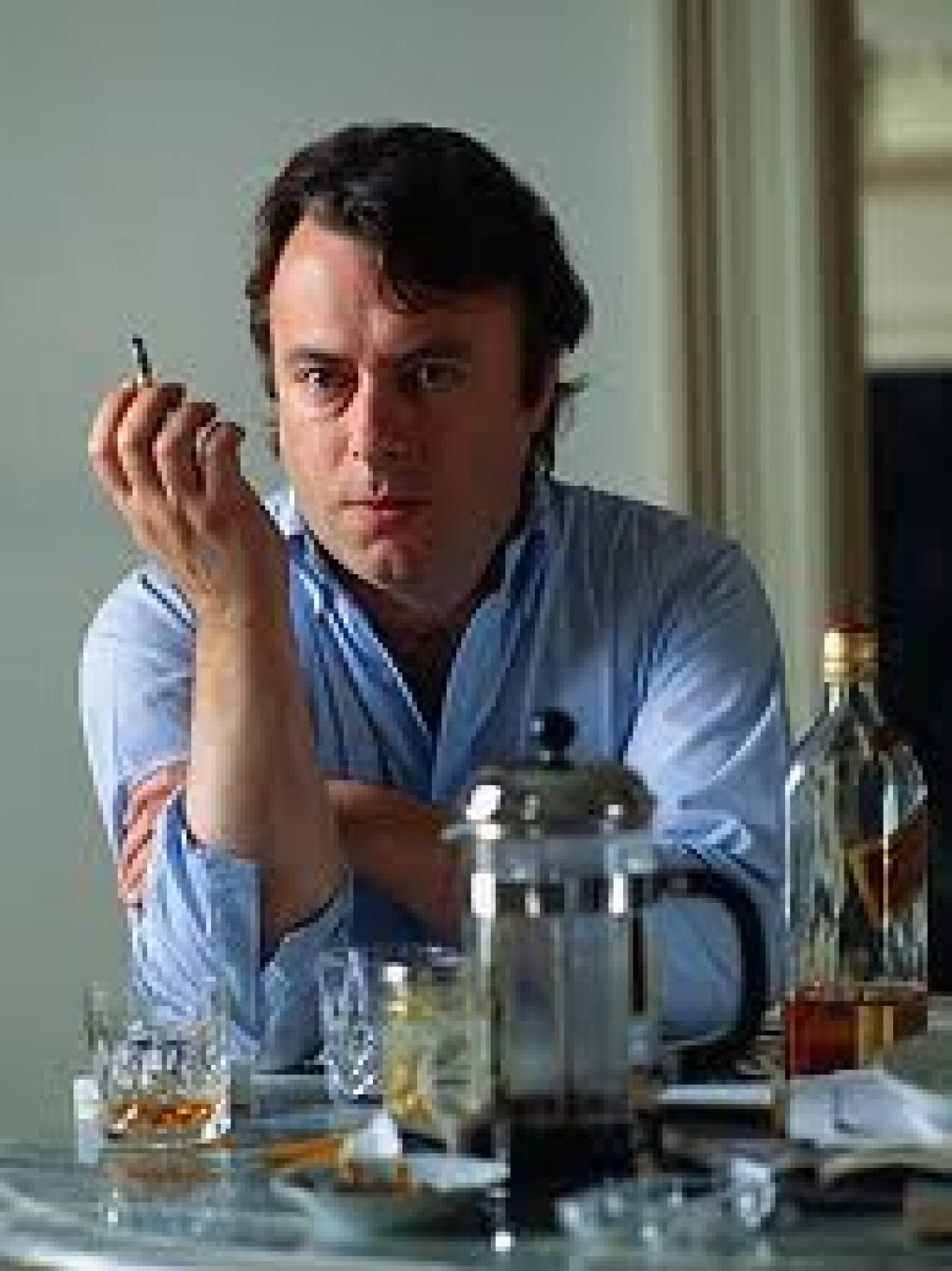 A picture of Hitchens at a table, smoking, surrounded by whisky and looking focused yet unimpressed (and gorgeous in my humble opinion)