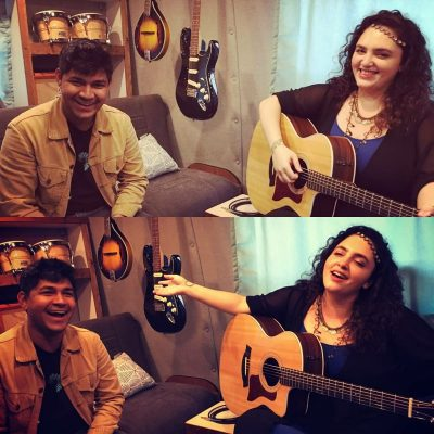 Shelley sitting in a recording studio van, holding a guitar, gesticulating wildly and laughing with Udayan, the engineer