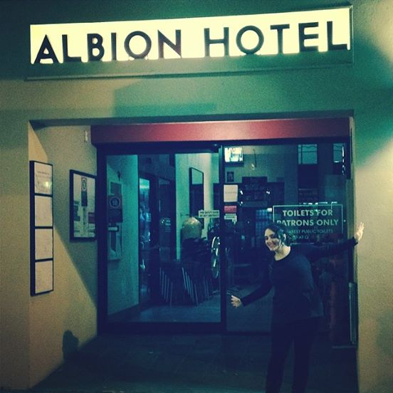 Pic of me outside the Albion Hotel, happy and arms out-streched